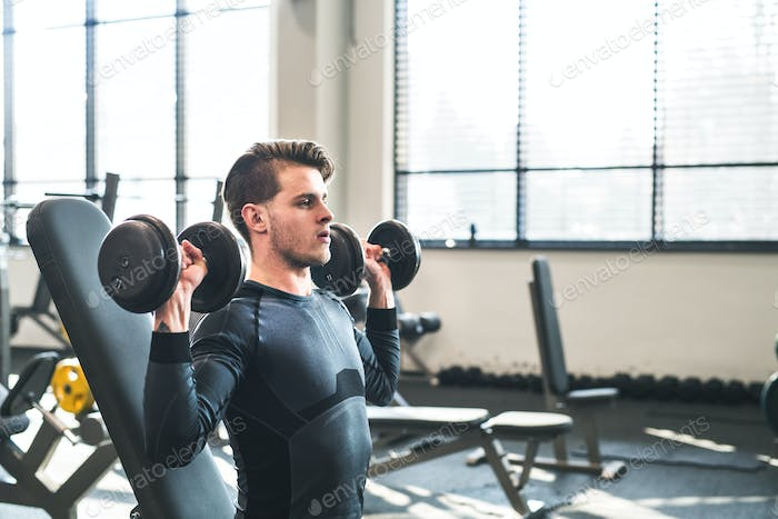 Young fit man in gym exercising with dumbbells. Copy space.