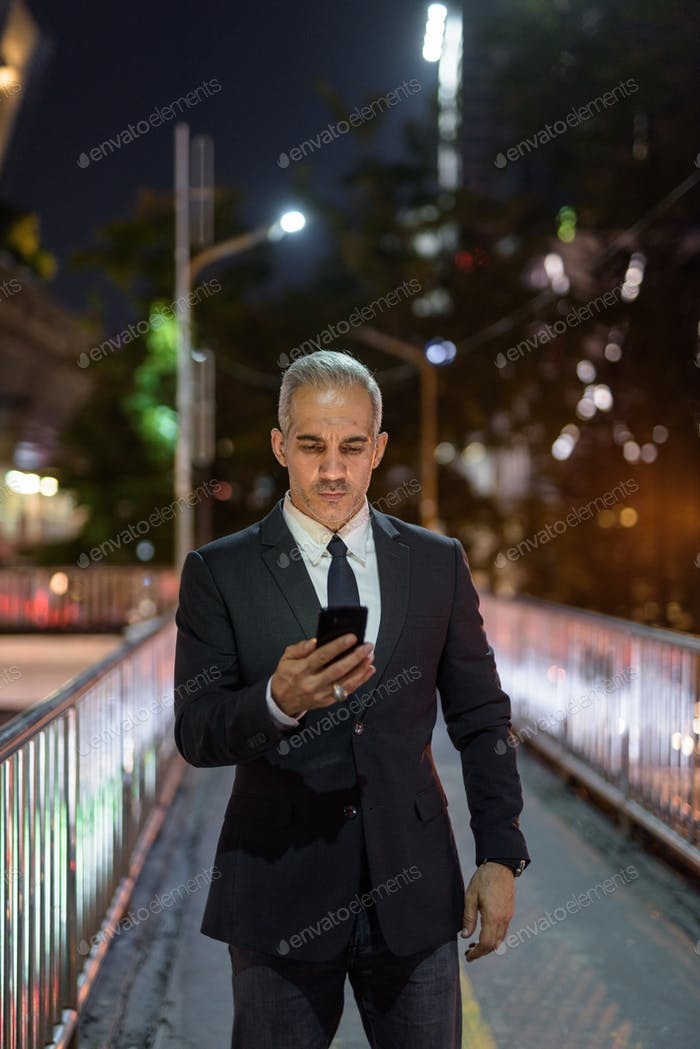 Businessman wearing suit in city at night while using mobile phone