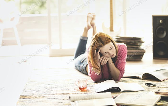 A woman lying on the floor reading a magazine.