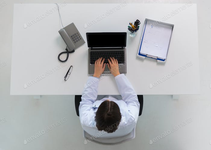 doctor typing on laptop at clinic