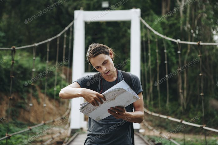 Confused Caucasian man looking at a map travel and explore concept