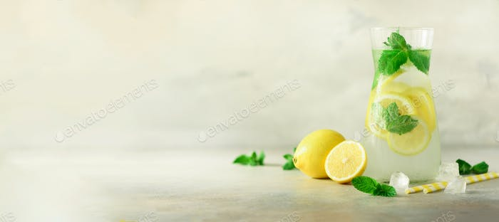 Detox water with mint, lemon on grey background. Banner with copy space. Citrus lemonade. Summer
