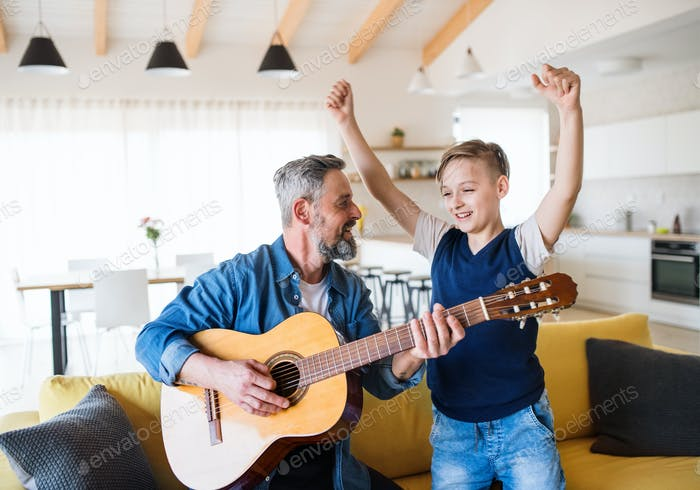 Mature father with small son sitting on sofa indoors, playing guitar