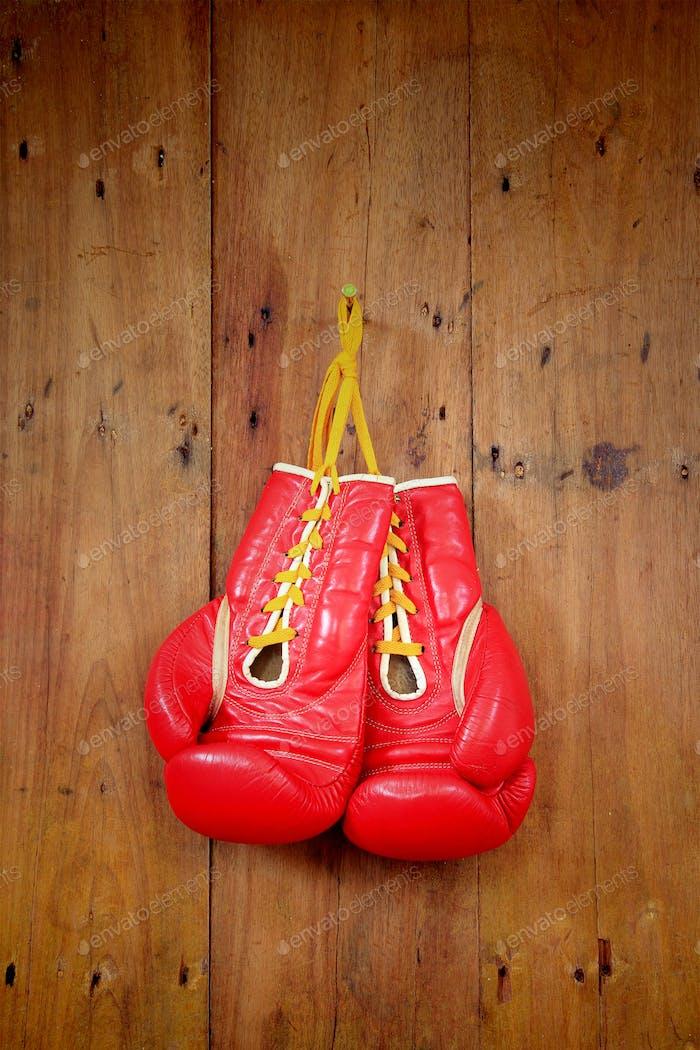 Boxhandschuh hängend auf hölzernem Hintergrund