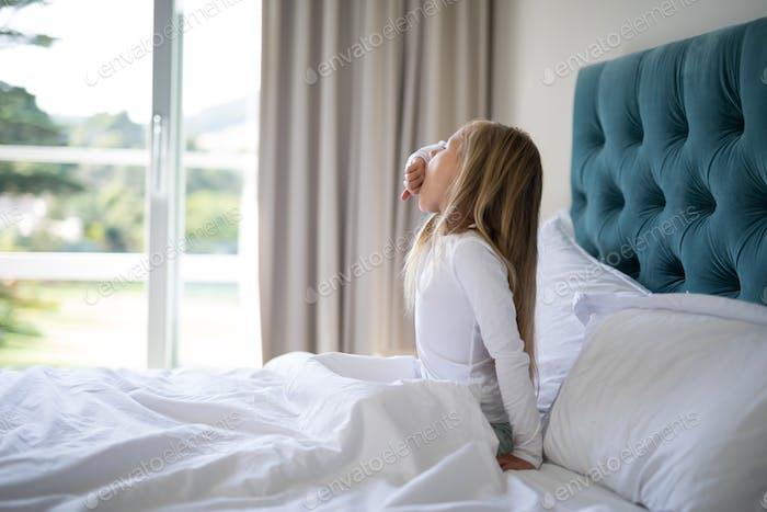 Girl yawning while waking up n bed
