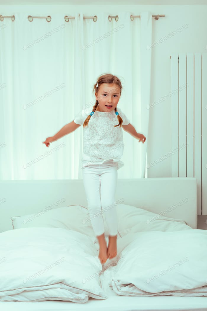 jumping child girl in bed