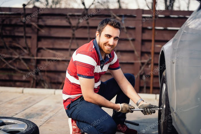 Close up smiling portrait of working man and changing tires using wrench, jack and hydraulic tools