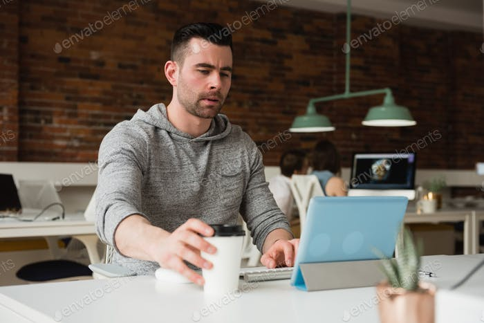 Male executive working on digital tablet while having coffee