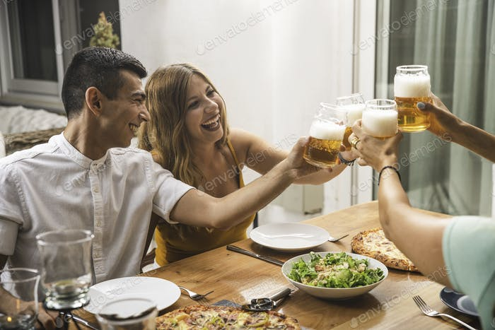 Happy Couple and Friends Toasting Beer and Laughing together
