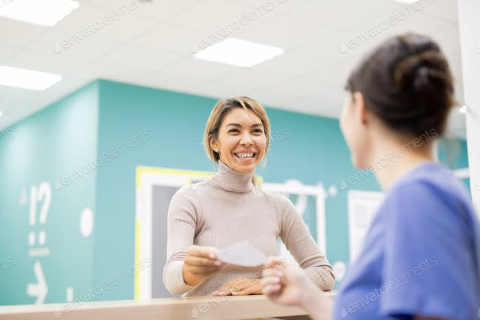 Young cheerful patient giving medical paper to receptionist or clinician
