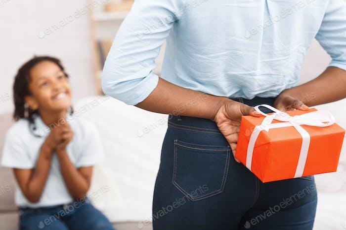 Afro mom hiding Chrismas gift for little kid