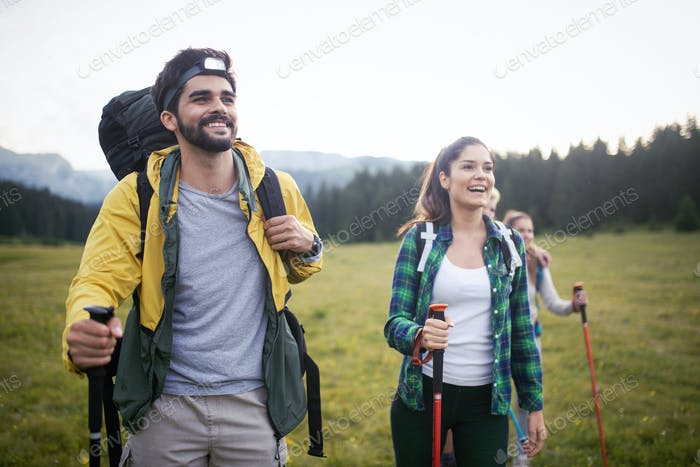 Backpackers happy young couple hiking with sticks