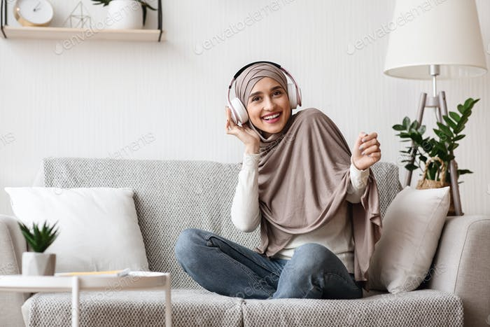 Arab girl sitting on sofa and listening music with wireless headphones