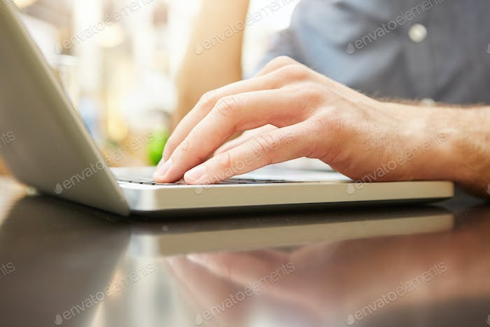 male hand typing on laptop at outside cafe