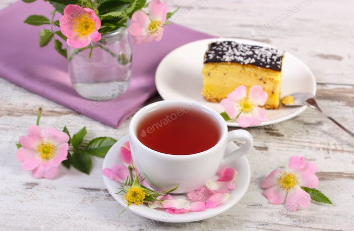 Cup of tea with cheesecake and wild rose flower on old board