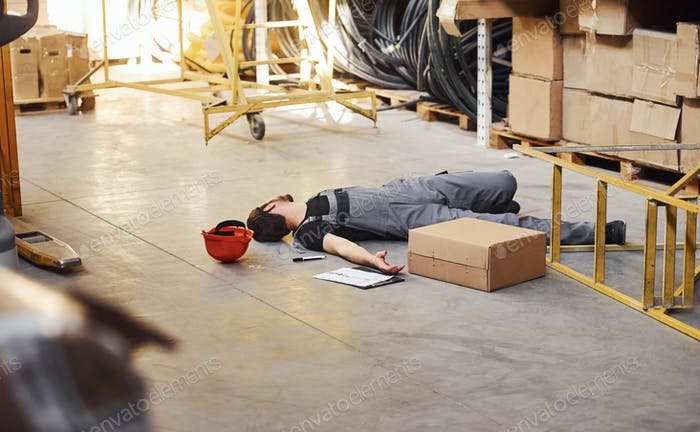 Warehouse worker after an accident in the storage. Man in uniform lying down on the ground