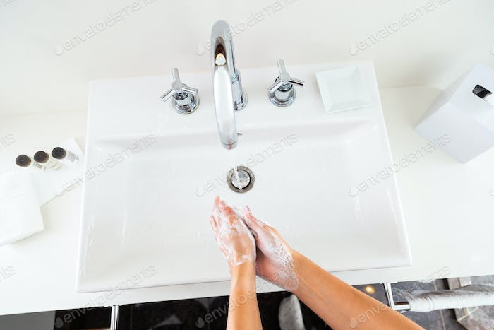 Washing hands with soap under the running water from above