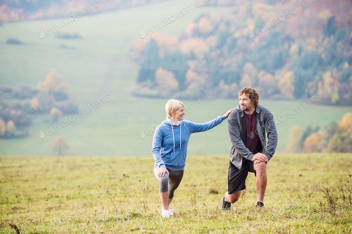 Zwei junge schöne Läufer im Herbst Natur, Stretching Beine