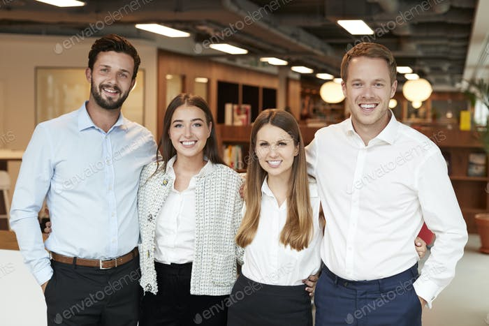 Portrait Of Young Businessmen And Businesswomen Standing In Modern Office