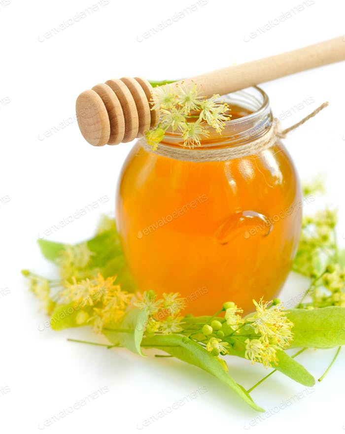 jar of fresh honey with flowers of linden on white background