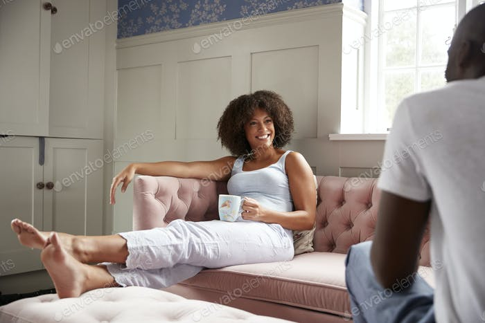 Young mixed race couple relax together drinking coffee in the morning, selective focus
