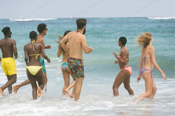 Rear view of multi ethnic group of friends enjoying and having fun on water at beach on sunny day