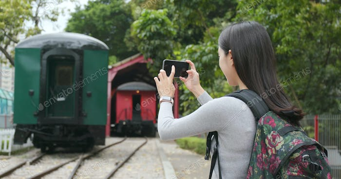 Tourist travel and taking phone on cellphone at train station