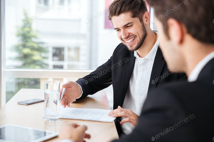 Two happy young businessmen sitting and working with documents together