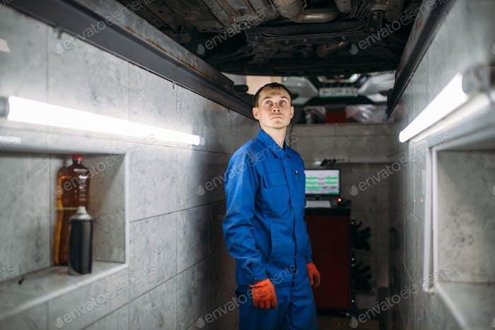 Mechaniker in der Grube überprüft Boden des Autos