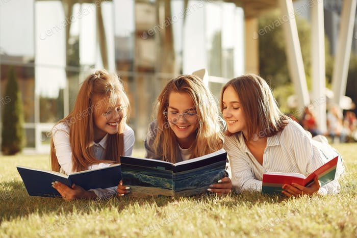 Three students lying on a grass with books