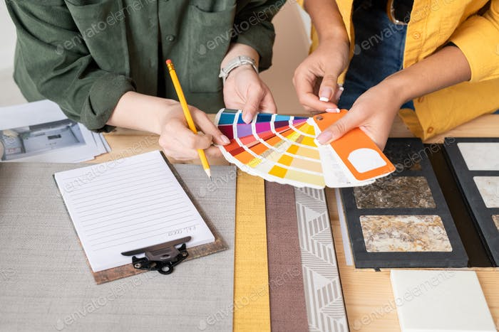 Hands of two young female interior designers consulting about choice of color