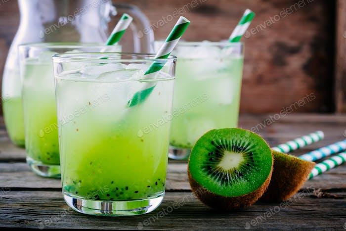Cocktail mit Kiwi und Minze in einem Glas auf hölzernem Hintergrund.