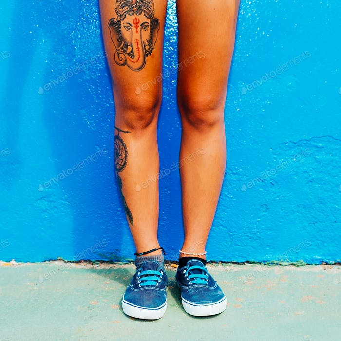 Spanish girl with a tattoo and stylish shoes on a blue wall. Ska
