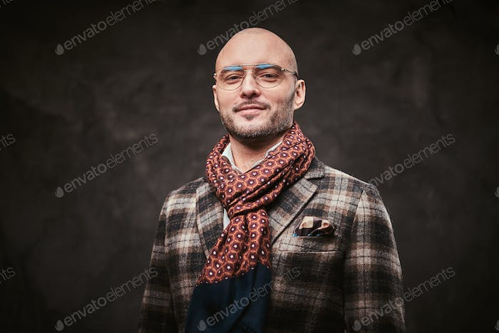 Succesful stylish businessman posing in a studio wearing checkered jacket, glasses and scarf