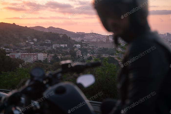 Selective focus shot of biker on sunset, sitting on his bike with beautiful city views
