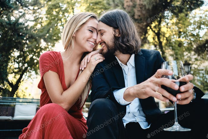 Beautiful sensual couple with glass of red wine happily talking on date in restaurant outdoor