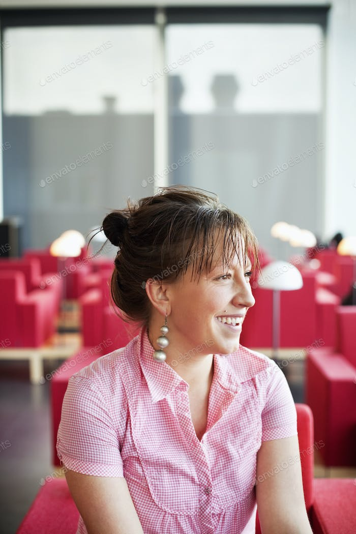 Close-up of smiling woman on red couch while looking away in cafe