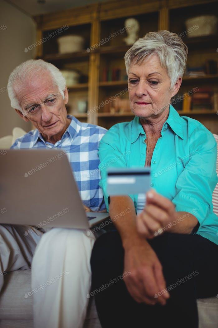 Senior couple doing online shopping on laptop