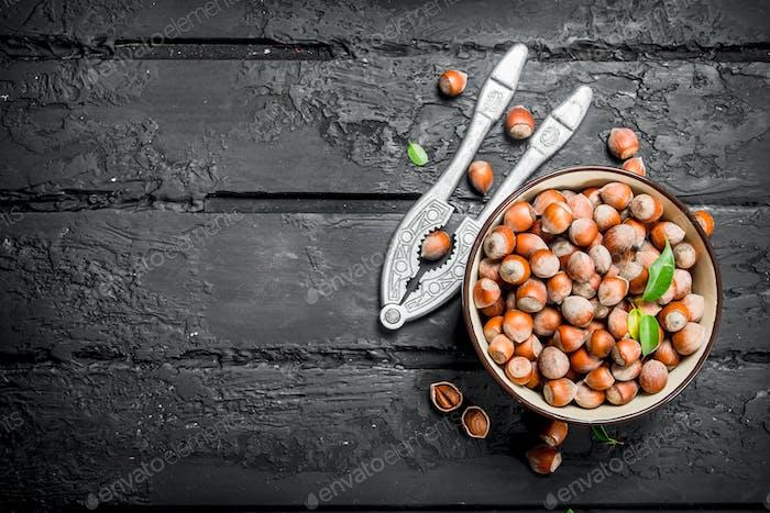 Hazelnuts in a bowl with a Nutcracker.
