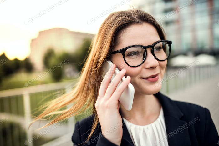 A young businesswoman with smartphone outdoors, making a phone call.