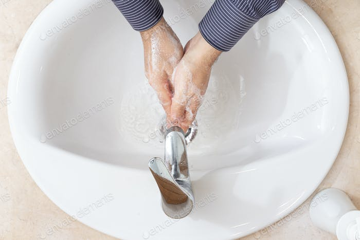 Man washing hands with water and soap on bathroom