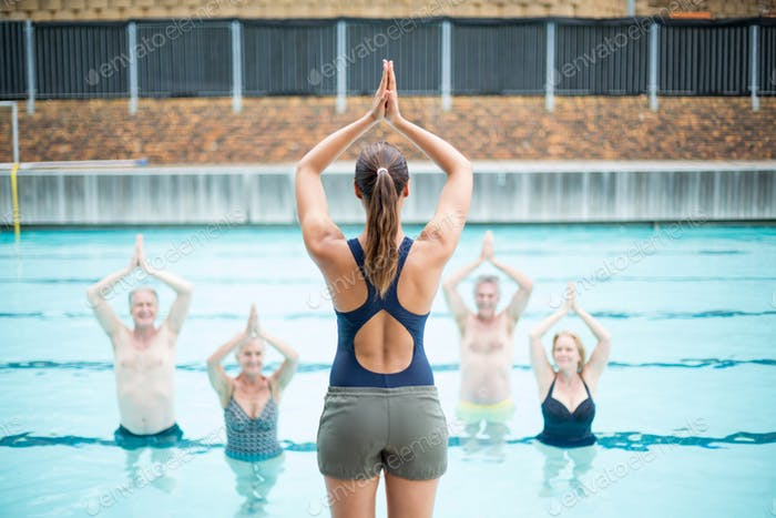 Rear view of female yoga instructor assisting senior swimmers