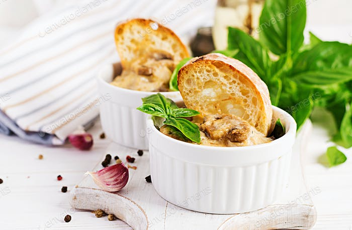 Baked mushroom julienne with chicken, cheese and toast in  pots.