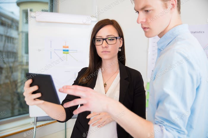 Colleagues Using Digital Tablet In Office