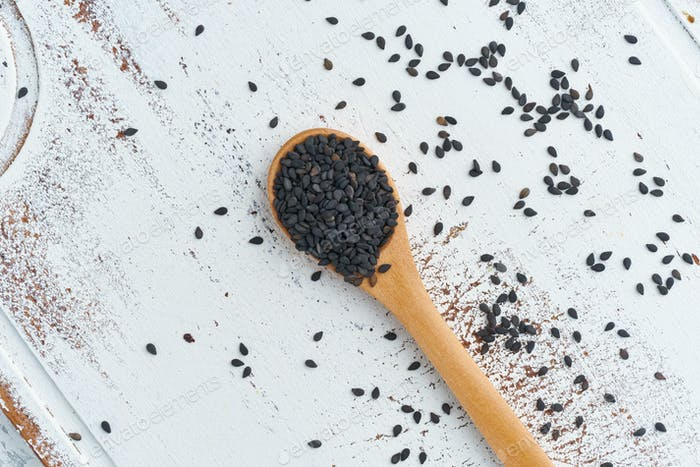 Black Sesame on wooden spoon. White wooden background. Top view, close up. Copy space.