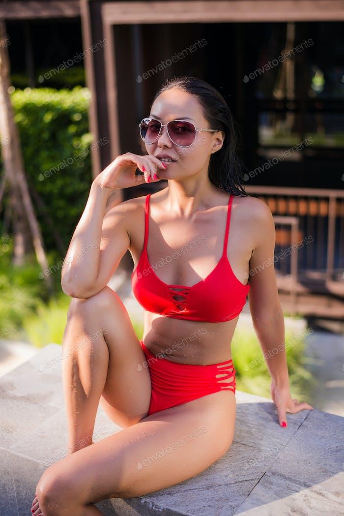Woman sunbathing in bikini at tropical travel resort. Beautiful young woman sit in a shadow at