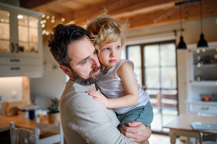 Отец с маленьким больным несчастным сыном в помещении дома, утешает его