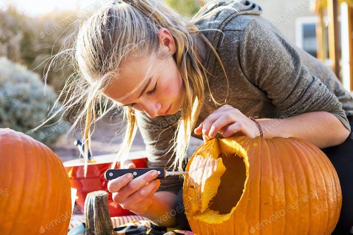 A teenage girl carving a large pumpkin at Halloween.