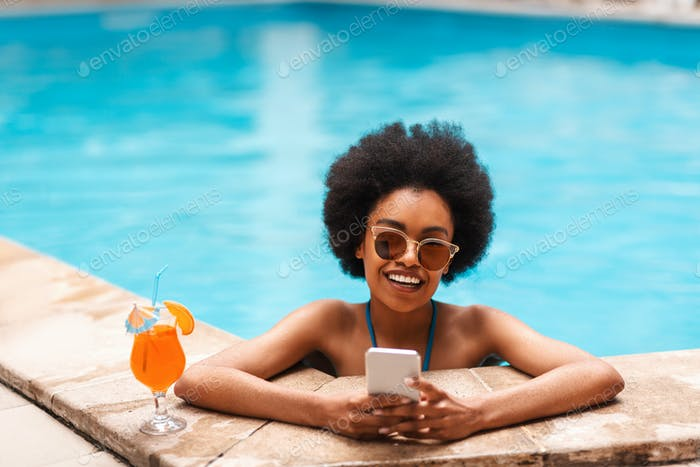 Joyful black girl with refreshing summer cocktail and smartphone relaxing in pool on sunny day