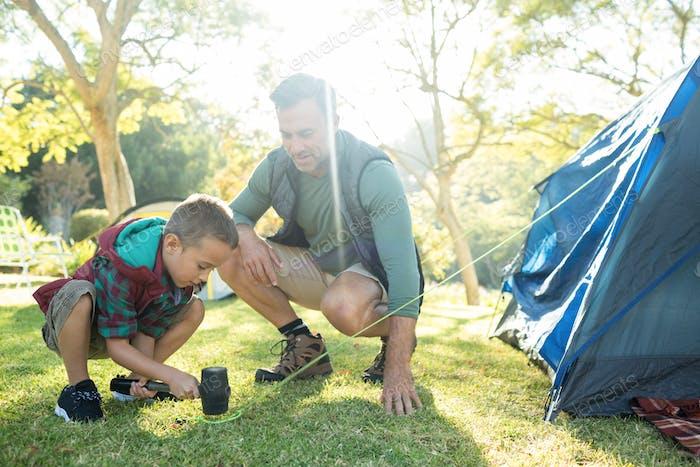 Vater und Sohn bauen das Zelt auf